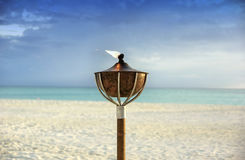 Burning torch on tropical beach Royalty Free Stock Photo