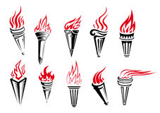 Burning torches set. Set of burning torches with fire flames isolated on white background in retro style Stock Images