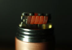 Burning triple staggered fused clapton coil in rebuildable dripping atomizer Stock Photos