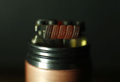 Burning triple staggered fused clapton coil in rebuildable dripping atomizer Royalty Free Stock Photo