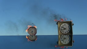 Burning  two old  clocks on mirror. Time is a fire. Burning  two old  alarm clocks on mirror in space. Time is a fire stock footage