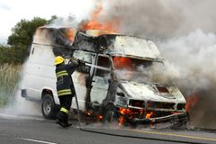 Burning Vehicle and Fireman Royalty Free Stock Photography