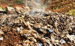 Burning waste or garbage in Africa. Pile of rubbish, garbage and various products, including lots of plastic, being burnt as a form of waste management in a Stock Photos