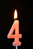 Burning wax candle as number four on black Stock Photography