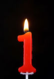 Burning wax candle as number one on black Royalty Free Stock Photo