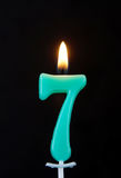 Burning wax candle as number seven on black Royalty Free Stock Images