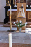 Burning wax candle in cathedral - religion background, focus on foreground Royalty Free Stock Images