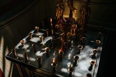 Burning wax candle in the dark in church stock images