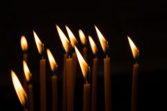 Burning wax candles against the window in a dark room royalty free stock photo