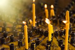 Burning wax candles in a Buddhist temple close-up. Rituals of worship of deities and gods in Asia. Meditation and worship of. Deities in Buddhism stock photography