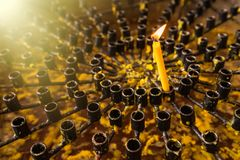 .Burning wax candles in a Buddhist temple close-up. Rituals of worship of deities and gods in Asia. Meditation and worship of. Burning wax candles in a Buddhist royalty free stock image