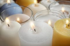 Burning wax candles of different shapes and colors. Closeup royalty free stock photo