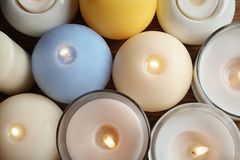 Burning wax candles of different shapes and colors. Top view royalty free stock images