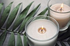 Burning wax candles and tropic leaf. On table royalty free stock photo