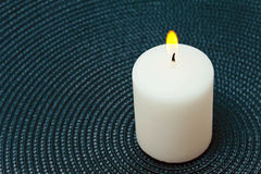 Burning white candle on a blue background Royalty Free Stock Photos