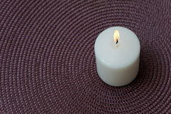 Burning white candle on a purple background Stock Photography