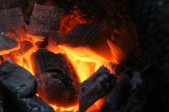 Burning wood coals. A craftsman/blacksmith working metal the oldfashioned way, shot of his stoking fire Royalty Free Stock Photography