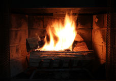 Burning wood in a fire place. Burning wood in a brick fire place Royalty Free Stock Photography