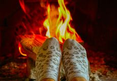 Burning wood at the fireplace, female legs in socks warming up. Firewood bricks at the fire, woman foot heating royalty free stock photography