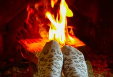 Burning wood at the fireplace, female legs in socks warming up. Firewood bricks at the fire, woman foot heating stock photos