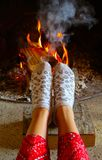 Burning wood at the fireplace, female legs in socks warming up. Firewood bricks at the fire, woman foot heating royalty free stock photo