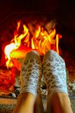 Burning wood at the fireplace, female legs in socks warming up. Firewood bricks at the fire, woman foot heating stock photo