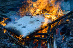 Burning wood, flame and smoke on blue background. Vivid Royalty Free Stock Photo