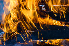 Burning wood, flame and smoke on blue background. Vivid Royalty Free Stock Images