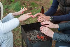 Burning wood in the grill and red coals with stream coming up from it. Little boy in red coat is warming his frozen hands above stock photography