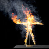 Burning wooden doll on desktop Stock Image