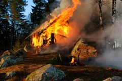Burning wooden house. In a coniferous forest royalty free stock image