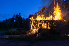 Burning wooden in house. Flame over a wooden house stock photo