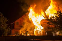Burning wooden house at night. Bright orange flames and dense sm. Oke from under the tiled roof on dark sky, trees silhouettes and residential neighbor cottage royalty free stock images