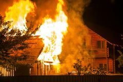 Burning wooden house at night. Bright orange flames and dense sm royalty free stock image