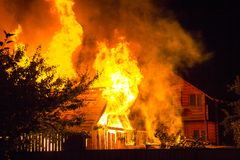 Burning wooden house at night. Bright orange flames and dense sm stock photo