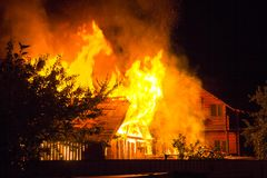 Burning wooden house at night. Bright orange flames and dense sm stock photography