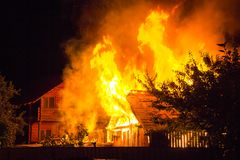 Burning wooden house at night. Bright orange flames and dense sm stock image