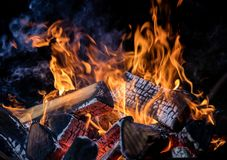 Burning wooden logs in fire, campfire on black. Burning wooden logs in fire, campfire isolated on black background royalty free stock photography