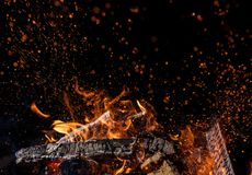 Burning wooden logs in fire, campfire on black. Burning wooden logs in fire, campfire isolated on black background stock photo