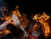 Burning wooden logs in fire, campfire on black. Burning wooden logs in fire, campfire isolated on black background royalty free stock images