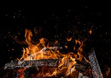 Burning wooden logs in fire, campfire on black. Burning wooden logs in fire, campfire isolated on black background royalty free stock photo