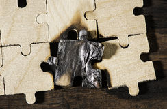 Burning wooden puzzle on dark background. Royalty Free Stock Image