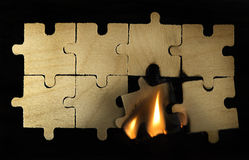 Burning wooden puzzle on dark background. Stock Photo