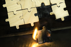 Burning wooden puzzle on dark background. Royalty Free Stock Photo