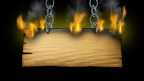 Burning Wooden Sign. With fire flames and smoke on an old wood plank with metal chains holding the signage as a western or rustic hot message advertisement on a Royalty Free Stock Photography