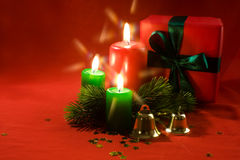 Burning xmas candle and little gift box Stock Photos