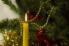 A burning yellow candle close-up against the backdrop of a New Year`s beautiful Christmas tree and a golden and red tinsel and be stock photos