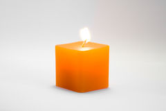 Burning yellow candle cube Royalty Free Stock Photos