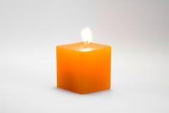 Burning yellow candle cube. Cute yellow burning candle cube on white background Royalty Free Stock Photos