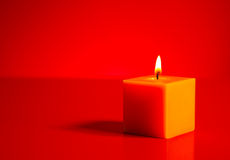 Burning yellow candle over red background Royalty Free Stock Image